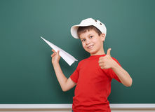 Schoolboy with paper plane play near a blackboard, empty space, education concept Stock Images