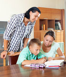 Schoolboy and parents together doing homework Stock Photo