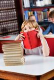 Schoolboy Peeking Through Book In Library. Portrait of cute little schoolboy peeking through book while sitting with stack of books at table in library stock photo