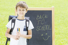 Schoolboy with pens and backpack against the blackboard. Education, Back to school concept Stock Photos