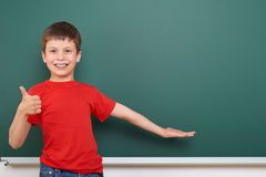 Schoolboy play near a blackboard, empty space, education concept Stock Images
