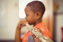 Schoolboy playing flute in classroom Stock Image