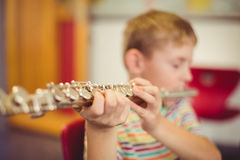 Schoolboy playing flute in classroom Royalty Free Stock Photo