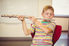 Schoolboy playing flute in classroom Stock Photo