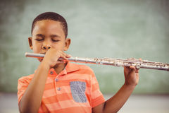 Schoolboy playing flute in classroom Royalty Free Stock Image