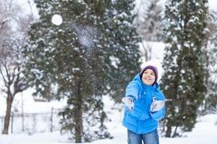 Schoolboy playing outside and throwing snowballs. Royalty Free Stock Photography