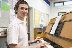 Schoolboy playing piano in music class Royalty Free Stock Image