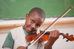 Schoolboy playing the violin. In a classroom stock photos