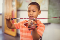 Schoolboy playing violin in classroom Stock Photo