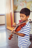 Schoolboy playing violin in classroom Royalty Free Stock Photography