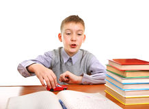 Schoolboy plays with a Toy. On the School Desk on the white background Royalty Free Stock Photo