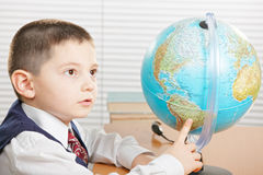 Schoolboy pointing at globe Royalty Free Stock Images