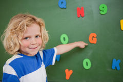 Schoolboy pointing at a letter. On a blackboard Stock Photography