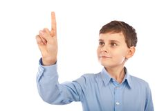 Schoolboy pointing to the copyspace. Schoolboy pointing or putting the finger on an imaginary item in the copyspace Royalty Free Stock Image