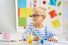 Schoolboy. Portrait of little schoolboy in glasses sitting at the desk royalty free stock images