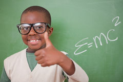 Schoolboy posing with the the mass-energy formula. Schoolboy posing with the the mass-energy equivalence formula and the thumb up in front of a blackboard Royalty Free Stock Photography
