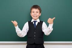 Schoolboy posing at school board, empty space, education concept Stock Photos