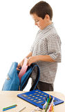 Schoolboy prepare the schoolbag. Schoolboy putting an exercise book in a blue color schoolbag - isolated Stock Image