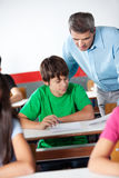 Schoolboy And Professor Looking At Paper During. Teenage schoolboy and professor looking at paper during examination in classroom Stock Photo
