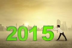 Schoolboy pushing number 2015. Little boy pushing number 2015, symbolizing happy new year royalty free illustration