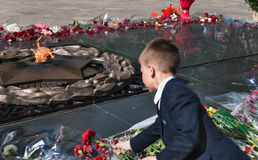 Schoolboy put flowers to the eternal fire at the memorial Stock Images