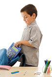 Schoolboy putting a calculator in the schoolbag Stock Image