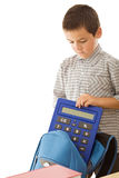 Schoolboy putting a calculator in the schoolbag Royalty Free Stock Image