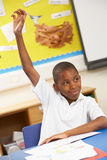 Schoolboy Raising Hand In Classroom. Smiling Stock Photo