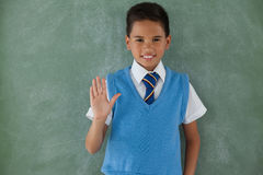 Schoolboy raising hand in classroom. Portrait of schoolboy raising hand in classroom at school Stock Photography