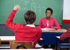 Schoolboy Raising Hand In Classroom. Rear view of schoolboy raising hand with female teacher in background at classroom Royalty Free Stock Photos