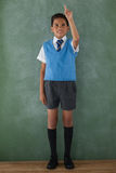 Schoolboy raising hand in classroom. At school Royalty Free Stock Images
