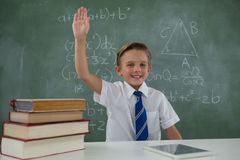 Schoolboy raising hand while sitting in classroom Stock Photo