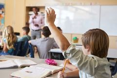 Schoolboy raising hand to answer question in a school class royalty free stock photos