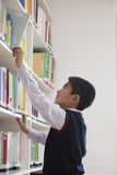 Schoolboy reaching for book off bookshelf Stock Photography