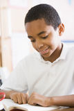 Schoolboy reading a book in class Royalty Free Stock Photo