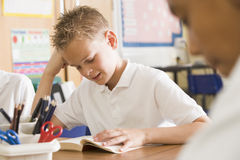 Schoolboy reading a book in class Stock Photography