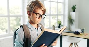 Schoolboy reading book. Schoolboy in eyewear and backpack reading book in classroom, diligent pupil studying, absorbing knowledge stock footage
