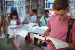 Schoolboy reading book with his classmates studying in background. At school Stock Photography