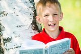 Schoolboy reading the book at  nature Royalty Free Stock Image