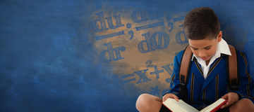 Composite image of schoolboy reading book over white background Royalty Free Stock Photography
