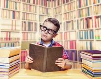 Schoolboy reading book in the school library Stock Photos