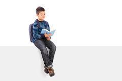 Schoolboy reading a book seated on signboard Royalty Free Stock Photography