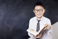 Schoolboy reads book while standing. Portrait of adorable little boy reading a book while standing in the classroom and smiling at the camera Stock Images