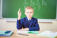 Schoolboy ready to answer and raised hand up Royalty Free Stock Photo