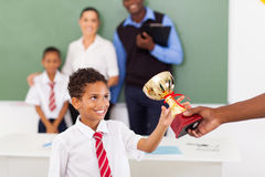 Schoolboy receiving trophy. Elementary schoolboy receiving a trophy in classroom with teachers and classmate stock photo