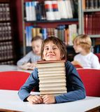 Schoolboy Resting Chin On Stack Of Books. Portrait of cute little schoolboy resting chin on stack of books at table in library with classmates in background Stock Photography