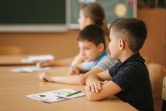 Schoolboy rise hand in classroom. Elementary school. Education.  royalty free stock photo