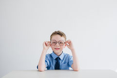 Schoolboy in school uniform and glasses sitting at the Desk Stock Photos