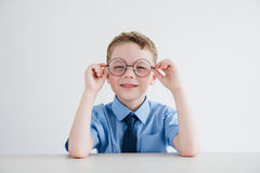 Schoolboy in school uniform and glasses sitting at the Desk Royalty Free Stock Photos