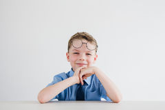Schoolboy in school uniform and glasses sitting at the Desk Royalty Free Stock Images